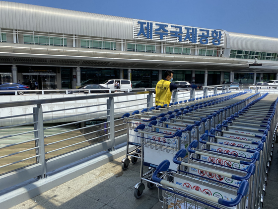 제주국제공항 직원이 코로나19 확산을 대비해 관광객용 카트를 소독하고 있다. 최충일 기자