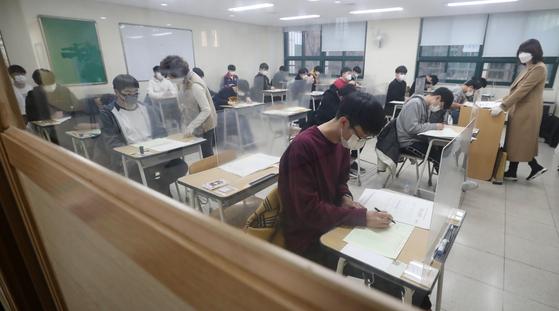 2021학년도 대학수학능력시험이 치러진 3일 오전 서울 종로구 경복고등학교에 고사장에서 수험생들이 시험지를 받고 답안지에 마킹하고 있다. [사진공동취재단]