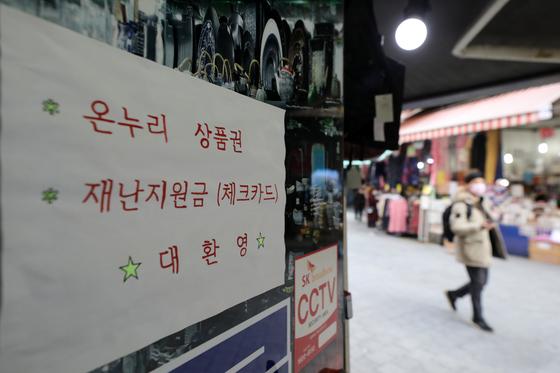 지난달 서울 중구 남대문시장의 한 상가에 재난지원금 사용 가능 안내문이 붙어있다. 뉴스1