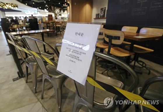 수도권 사회적거리두기 2단계 격상 사흘째인 26일 서울 시내의 한 대형 쇼핑몰에 입점한 카페 테이블에 고객들의 취식을 막는 테이프가 설치돼 있다. [연합뉴스]