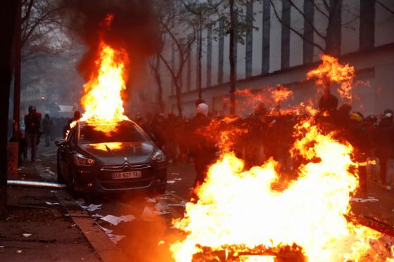 5일 프랑스 파리에서 '포괄적 보안법' 반대 시위가 벌어져 시위 현장의 차량이 불길에 휩싸여 있다. 로이터=연합뉴스