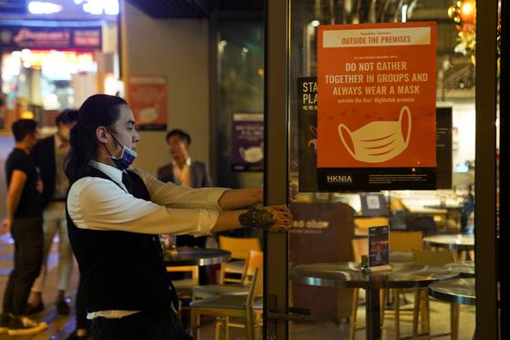 한 남자가 홍콩 식당에서 가게를 스캔합니다.  최근 확인 된 코로나 바이러스의 수가 급증하면서 홍콩의 나이트 클럽과 같은 엔터테인먼트 시설을 폐쇄하기로 결정했습니다. [로이터=연합뉴스]