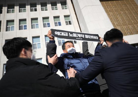 8일 오전 서울 국회 본관 앞 계단에서 민주노총 조합원들이 국제노동기구(ILO) 핵심협약 비준, 중대재해기업처벌법 제정 등을 촉구하는 기자회견을 하다 관계자들의 제지를 받고 있다. 연합뉴스