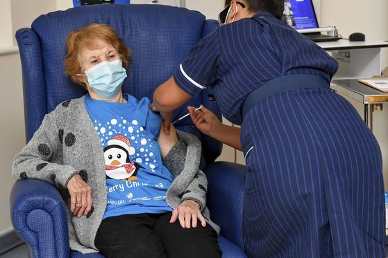 90세인 마거릿 키넌(왼쪽)이 영국에서 8일(현지시간) 처음으로 화이자 백신을 맞았다. 의료진이 키넌의 어깨 쪽에 백신을 투여하는 모습. [AP=연합뉴스]