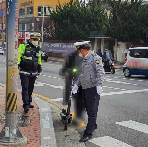 10일 오후 3시 30분경 경찰이 전동킥보드를 탄 채 횡단보도를 건넌 시민을 길가에 불러세워 범칙금을 부과했다. 편광현 기자