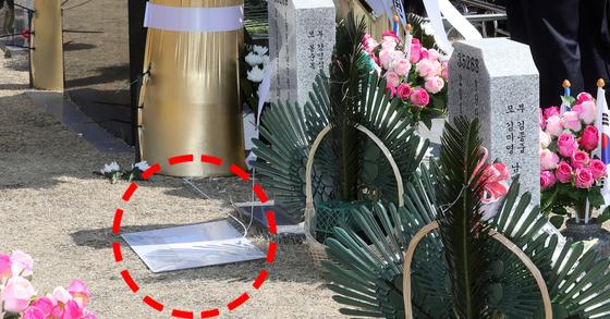 지난해 3월 22일 국립대전현충원 천안함 46용사 묘역 한켠 바닥에 문재인 대통령 화환 명판이 뒤집힌 채 놓여 있다. 이 명판은 당시 황교안 자유한국당 대표 참배 후 제자리에 붙었다. [연합뉴스]