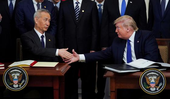 지난 1 월 미국 백악관에서 1 단계 米 중 무역 협정 서명 당시 류호 중국 부총리 (왼쪽)와 트럼프 대통령이 악수하고있다. [로이터=연합뉴스]