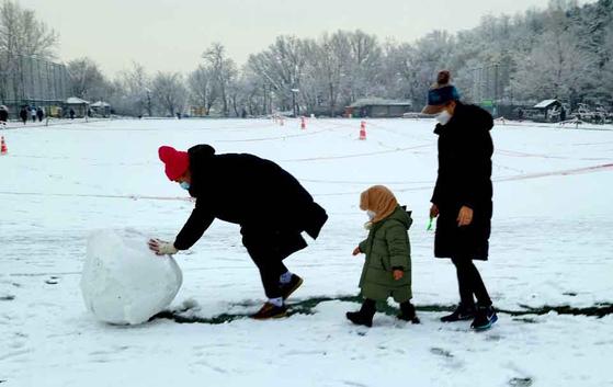 13일 오전 서울 양천구 목동 용왕산 공원에서 한 가족이 눈사람을 만들기 위해 눈을 굴리고 있다. 변선구 기자