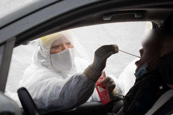 13일 강원 강릉아이스아레나 주차장에 마련한 드라이브스루 선별진료소에서 현장 의료진이 시민들의 검체를 채취하고 있다. 뉴스1