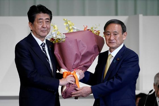 아베 신조 전 일본 총리(왼쪽)가 지난 9월 14일 자민당 총재 선거에서 새 총재에 선출된 스가 요시히데 당시 관방장관에게 꽃다발을 건네고 있다. [로이터=연합뉴스]