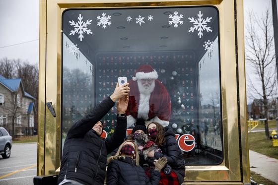 13일(현지시간) 캐나다 온타리오주 본에서는 산타클로스가 이동식 유리 상자 안에 들어가 어린이들을 만났다. 코로나19 감염을 막기 위한 조치다. 당초 열릴 예정이던 대대적인 산타 대면 행사는 코로나19 유행으로 취소됐다. AP=연합뉴스