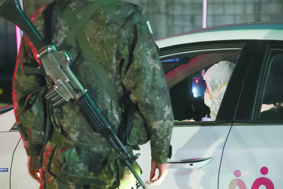 경기도 연천군 육군 모부대의 위병소 병사가 방역당국 관계자의 부대 출입 절차를 확인하고 있다. [연합뉴스]