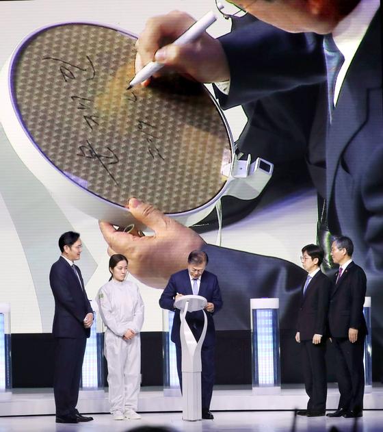 문재인 대통령이 지난해 4월 삼성전자 화성 캠퍼스에서 열린 시스템반도체 비전 선포식에 참석해 세계 최초 EUV(극자외선) 공정 7나노로 출하된 웨이퍼 칩에 서명하고 있다. 연합뉴스.