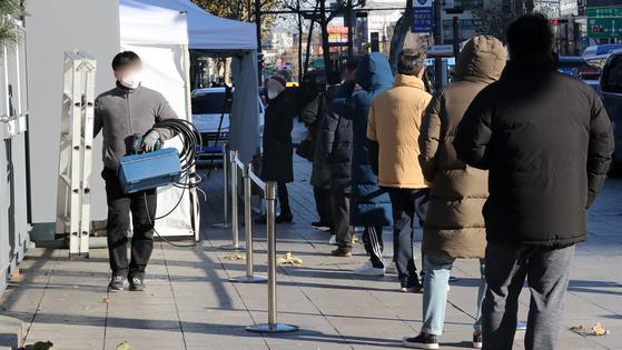 14일 서울 종로구 탑골공원 앞에 마련한 신종 코로나바이러스 감염증(코로나 19) 임시 선별진료소에서 시민들이 검사를 기다리고 있다. 뉴스1
