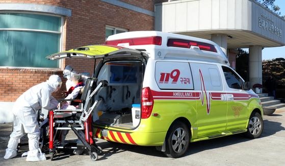코로나19 집단감염이 발생한 전북 김제시 가나안요양원에서 15일 119 구급대원들이 한 확진 환자를 병원으로 이송하고 있다. [뉴스1]