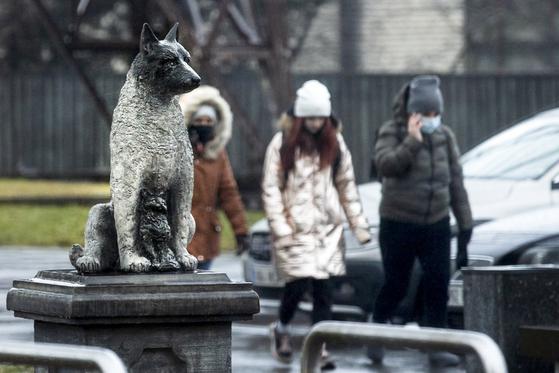 주민들은 유렉 동상 뒤를지나갑니다.  AP = 연합 뉴스