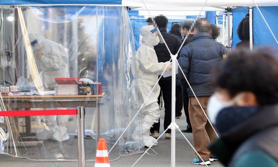 대구 지역 확진자가 증가세를 보이는 지난 14일 오후 대구 수성구보건소 선별진료소에서 의료진이 분주하게 신종 코로나바이러스 감염증(코로나19) 검사를 하고 있다. 연합뉴스