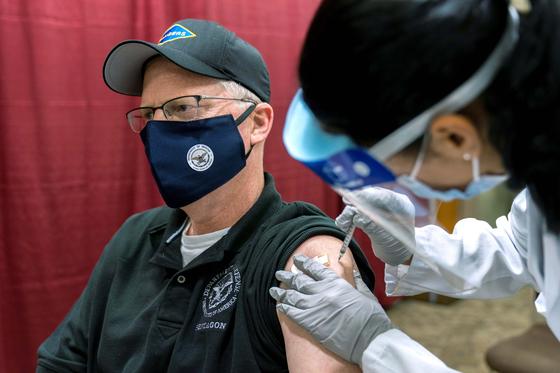 크리스토퍼 밀러 미국 국방장관 대행이 신종 코로나바이러스 감염증 백신접종 첫날인 14일 메릴랜드주 베데스다의 월터 리드 군병원에서 화이자 백신을 맞고 있다. [로이터]