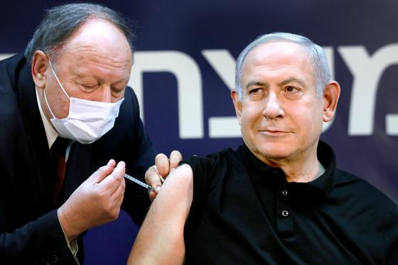베냐민 네타냐후 이스라엘 총리가 지난 19일(현지시간) 텔아비브 인근 시바 메디컬센터에서 화이자 백신을 맞고 있다. 백신에 대한 국민 불안감을 줄이기 위해 네타냐후 총리는 백신 접종 과정을 생중계했다. [로이터=연합뉴스]