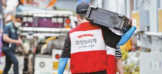 지난 7월 대전광역시 서구의 풍수해 현장에서 희망브리지 직원 및 자원봉사자가 흙탕물에 잠긴 가재도구의 정리를 돕고 있다. [사진 희망브리지]