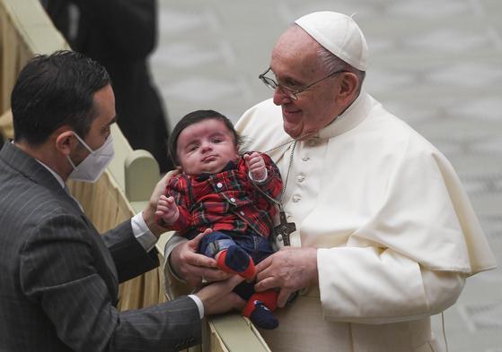 21일(현지시간) 프란치스코 교황이 크리스마스를 앞두고 열린 특별알현에서 교황청 직원의 아이를 안고 있다. EPA=연합뉴스