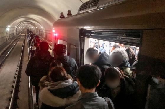 21일 오후 6시 30분쯤 김포 골드라인 경전철이 김포공항역에서 고촌역사이에서 멈춰서 시민들이 큰 불편을 겪고 있다. 이 차량에 50여분간 갇혀 있던 약 400여명의 승객들이 열차 선로 위 비상통로로 고촌역까지 걸어가고 있다. 뉴스1