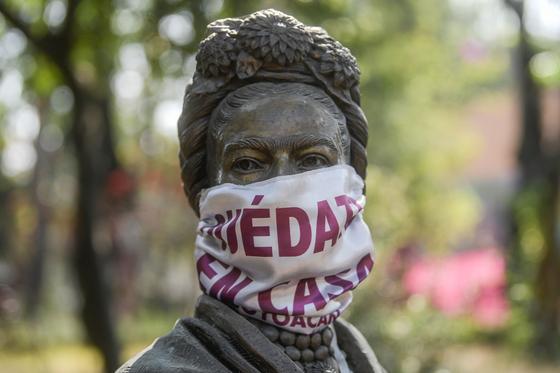 """멕시코의 대표 화가인 프리다 칼로 조각상에 """"집에 머물러라""""는 마스크가 씌워졌다. [AFP=연합뉴스]"""