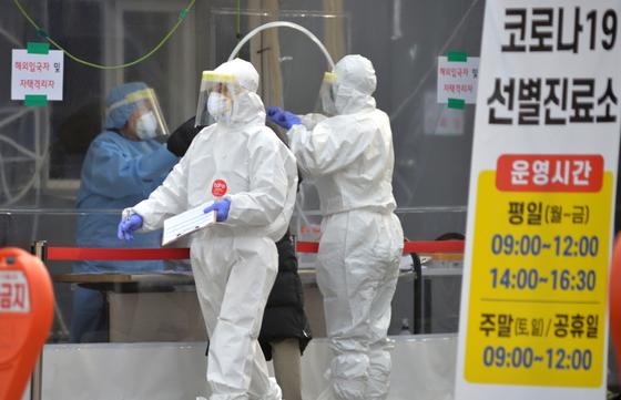 신종 코로나바이러스 감염증(코로나19) 신규 확진자가 1092명으로 역대 두번째 많이 발생한 23일 대전의 한 보건소에 마련된 코로나19 선별진료소에서 의료진들이 시민들을 검사하고 있다.김성태/2020.12.23.