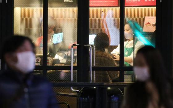 일본에서 신종 코로나바이러스 감염증(코로나19)이 확산하는 가운데 지난 16일 도쿄도(東京都)의 한 커피숍에서 마스크를 쓴 종업원이 비닐 차단막을 사이에 두고 주문을 받고 있다. [연합뉴스]