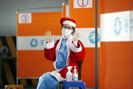 크리스마스를 하루 앞둔 24일 광주 북구 선별진료소에서 산타복을 입은 의료진이 검체 채취를 하러 온 시민들을 반갑게 맞이하고 있다. 뉴스1