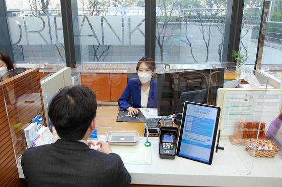 신종 코로나바이러스 감염증(코로나19) 확산 방지 차원에서 28일부터 은행 영업점 대기고객 수가 10명으로 제한된다. 사진은 지난 4월 전국 모든 영업점 고객창구에 투명 칸막이를 설치한 우리은행. 우리은행