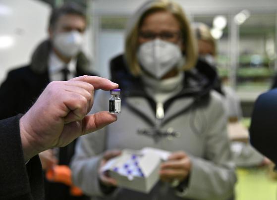 오스트리아 비엔나에서 시청 관계자가 26일 도착한 코로나 백신을 손으로 들어보이고 있다. 오스트리아에서는 27일부터 요양원 거주자 등을 대상으로 1단계 접종이 시작된다. [AFP=연합뉴스]