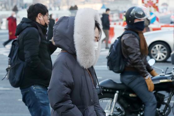 21일 오전 서울 종로구 광화문 네거리에서 두꺼운 겨울옷을 챙겨입은 시민들이 출근길 발걸음을 재촉하고 있다. 뉴스1