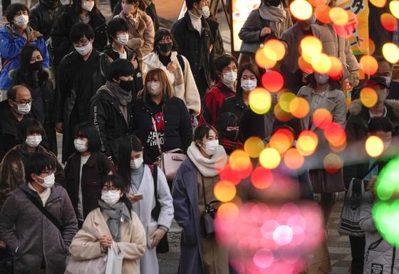 26일 마스크를 쓴 시민들이 크리스마스 일루미네이션이 장식된 도쿄 번화가를 지나고 있다. 이날 도쿄에선 역대 최다인 949명의 코로나19 하루 확진자가 나왔다. [EPA=연합뉴스]