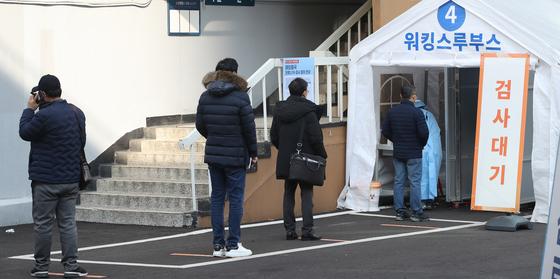 27일 서울 중구 국립중앙의료원 신종 코로나바이러스 감염증(코로나 19) 선별진료소를 찾은 시민들이 검사받기 위해 줄서 있다. 뉴스1