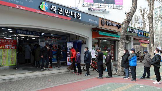 지난 3월 오후 서울 노원구의 한 복권 판매점에서 로또복권 구매를 위해 줄지어 서있다. 뉴시스