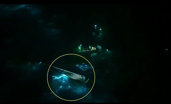 29일 오후 7시44분쯤 제주도 북서쪽 해상에서 전복된 어선(원안)에 해경 구조대가 접근해 선원들을 구조하고 있다. [사진 제주해경]