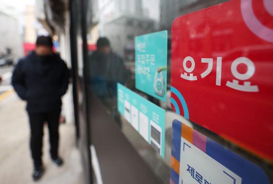 독일 딜리버리히어로(DH)가 공정거래위원회 요구를 받아들여 한국 배달 앱 1위 '배달의민족'을 인수하기 위해 2위 '요기요'를 매각하기로 했다. 29일 오후 서울 시내 한 음식점에 나란히 부착된 배달의 민족·요기요 광고. 연합뉴스