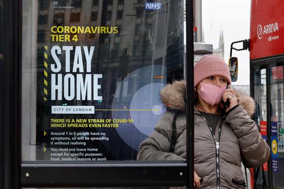 코로나 4단계 제한조치가 내려져 있는 영국 런던에서 29일 한 여성이 마스크를 쓰고 버스를 기다리고 있다. 조만간 영국에서 이보다 강화된 5단계 조치가 내려질 것이라는 보도가 나왔다. 5단계에서는 학교가 문을 닫고 모두가 자택에서 대기해야 한다. [AFP=연합뉴스]