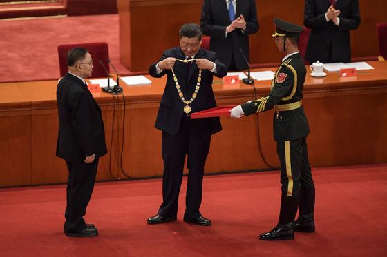 지난 9월 8일 베이징 인민대회당에서 열린 '전국 코로나19 퇴치 표창 대회'에서 시진핑 주석이 장보리(張伯禮·72·왼쪽) 중국 공정원 원사에게 '인민영웅' 메달을 수여하고 있다. 중국은 이달 29일까지 확진자 9만6513명, 사망 4782명을 기록했다. [AFP=연합뉴스]