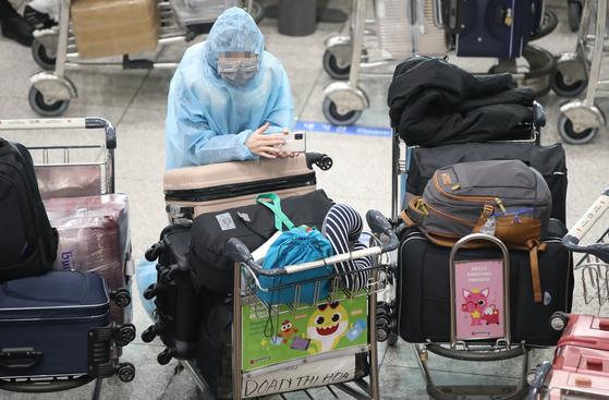 영국발 변이 코로나19 바이러스가 국내에서 확인되는 등 코로나19 확산이 계속되고 있는 28일 오전 인천국제공항 1터미널 입국장에서 방호복을 입은 해외 입국객이 대기하고 있다. 연합뉴스