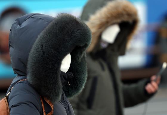 세밑 한파가 찾아온 30일 오전 서울 세종대로에서 시민들이 점퍼의 털모자를 쓰고 출근하고 있다. 연합뉴스