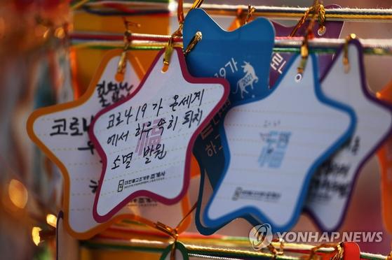 2021 새해 첫날인 지난 1일 오후 서울 종로구 조계사에 '코로나19가 끝나면 하고싶소'를 주제로 설치된 소원의 탑에 방문자들이 적은 새해 소망들이 매달려 있다. 연합뉴스