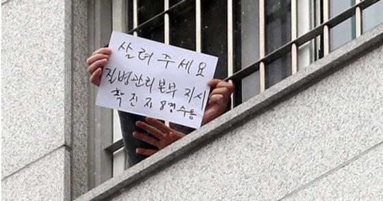 29일 서울 송파구 동부구치소에서 한 수용자가 자필로 쓴 글을 취재진에게 보여주고 있다. 뉴시스
