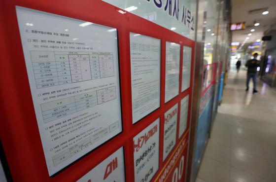 서울 송파구 한 부동산중개업소에 종합부동산세 개정 내용에 대한 안내문이 붙어있다.  연합뉴스