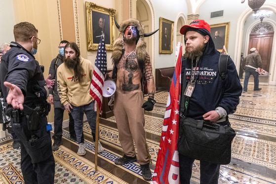 6일(현지시간) 버펄로 뿔 모자를 쓰고 미국 워싱턴 의회에 난입한 제이크 앤젤리(오른쪽 두번째)는 대표적인 큐어넌 신봉자로 알려져 있다.[AP=연합뉴스]