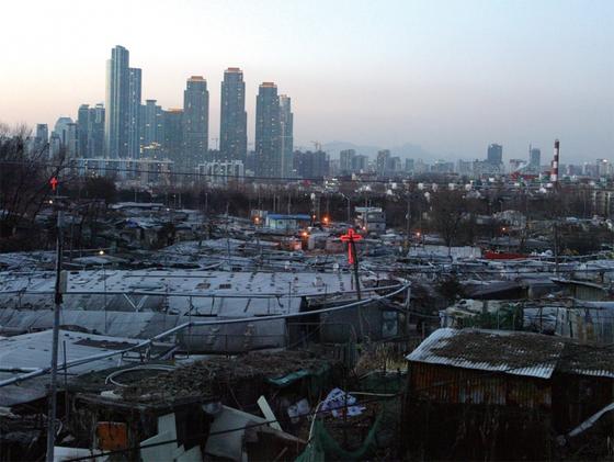 서울 강남 지역의 허름한 판잣집 저편에 초고층 주상복합이 보인다. 세상에 돈이 많이 풀릴수록 양극화는 극심해지고 있다.