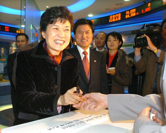 2005년 박근혜 당시 한나라당 대표가 부산 증권선물거래소를 방문,`동북아 물류 허브를 선도해 주시기 바랍니다`라는 글을 적은 뒤 환하게 웃고 있다. 중앙포토