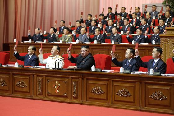 김정은 북한 국무위원장(가운데) 등 노동당 8차 대회에 참가한 대표자들이 대표증을 들어 당규약 개정에 찬성의 뜻을 표하고 있다. [뉴스1]