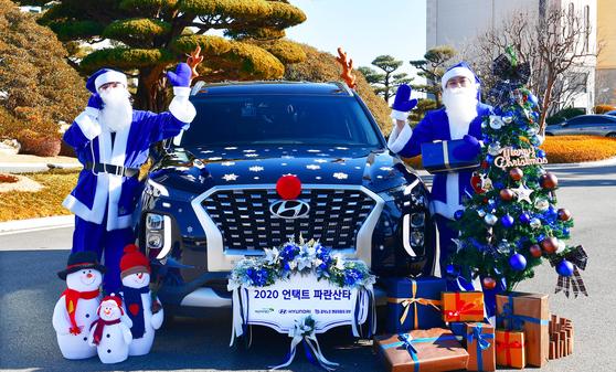 현대자동차가 지난해 12월 루돌프 장식을 한 파란 팰리세이드를 타고 소외 아동을 찾아가 선물을 전달하는 파란 산타 행사를 진행하는 모습. 사진 현대차